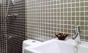 Stainless steel mosaic bathroom tiles add a luxurious and contemporary touch to this small bathroom