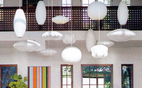 Decorative hanging lamps of various geometric shapes keep up the visual drama and accentuate the high ceiling