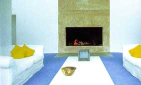 A beautiful white living area set off by the spare and cool granite fireplace and accented with warm lemon yellow and icy blue