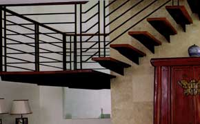 The use of clean lines for the railings brings out the sense of space and light for an otherwise solid staircase