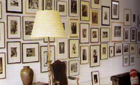 a loose gathering of black and white photographs makes a dramatic statement on the white painted wall