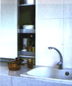 Kitchen utensils and condiments are hidden behind cabinets to save space